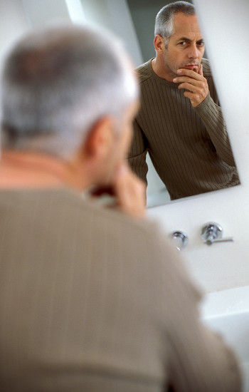 Man looking at himself questioningly in a mirror