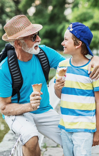 Grandfather and grandson chatting while eating ice cream